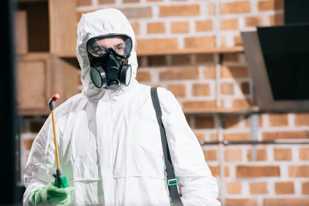 pest control worker standing with sprayer in kitchen and looking away